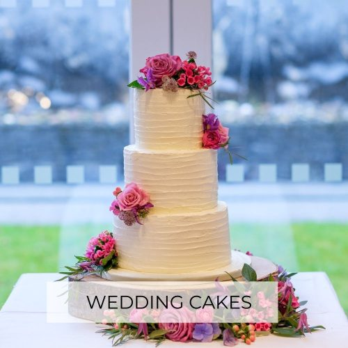 Three tier buttercream wedding cake with fresh flowers and wedding cakes title